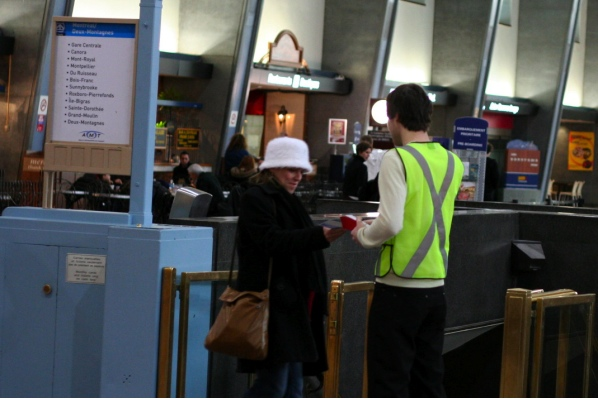 AMT employee hands out coupons at Central Station, complete with reflective vest (coupon disbursement is dangerous, don't you know?)