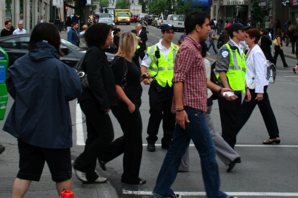 Police cadets wait until the last second before clearing pedestrian traffic for a speeding ambulance