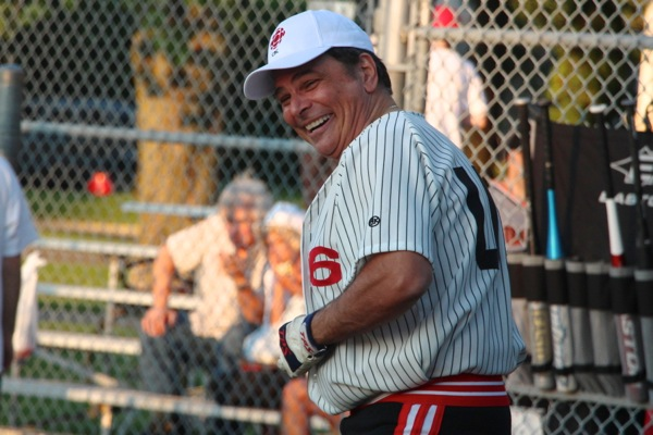Frank Cavallaro has to rebutton his shirt after it came apart during a swing of the bat.