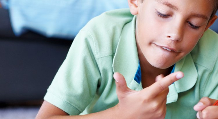boy counting on his fingers while doing homework