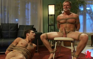 Gagged and tied up man has his cock hard while his gay partner is tied up on the floor