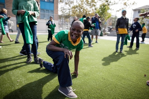 A happy boy smiles for the camera on the new playing field at the opening of a playground in Brooklyn.
