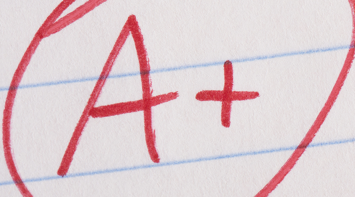 A plus (A+) grade written in red pen on notebook paper with the pen sitting there.