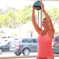 Danica performing a front shoulder raise using a medicine ball at LA Fitness - 3