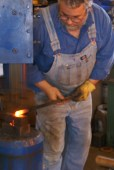 Using the air hammer on a thick piece of stock, Doug can shape quickly.