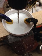 Mark center, and begin drilling with small bit, so you don't crack the lid.