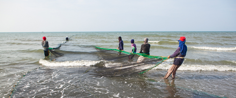 Filipino fishermen hauling their fishing net to shore.