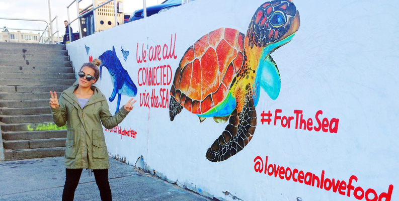 Surfer and artist Flick Palmateer in front of her World Oceans Day mural, Bondi Beach, Sydney, Australia