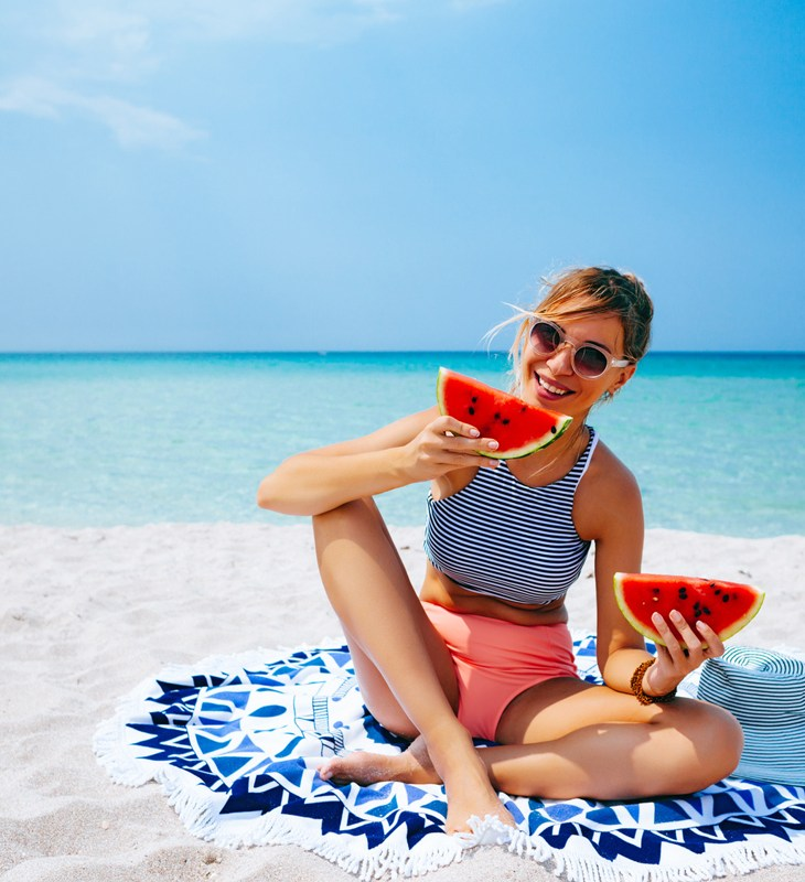 Woman eating watermelon on the beach in summer sunny day
