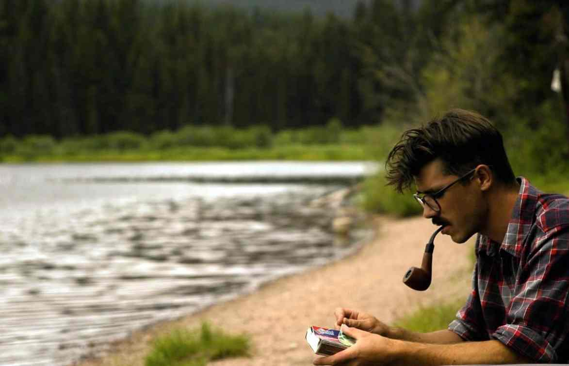 A young bespectacled man with a pipe and a book sitting by the woods and the lake, representing the idea of the modern day guerrilla UX designer