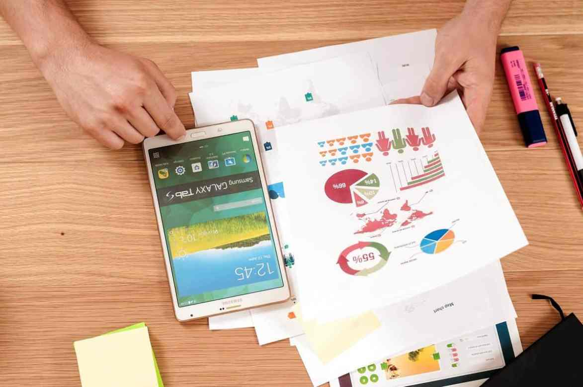 A designer using a phablet while reviewing user and market research insights