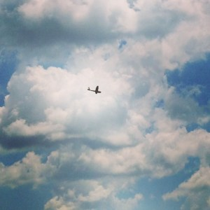 Silhouette of small plane against the clouds