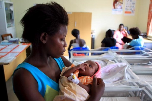 A mother holds her baby after breastfeeding at Kisenyi health centre in Uganda's capital Kampala April 10, 2015. Kisenyi health center in Kampala, which delivers 600 babies a month, symbolizes the shift in Uganda which has seen the country invest more money in the healthcare system to make it accessible for the poorest, Save the Children said. Child deaths in Kampala fell faster than in any other African city between 2006 and 2011 - despite a large influx of refugees from war-torn neighboring states, the charity said in a report. Picture taken April 10, 2015. To match HEALTH-CHILDREN/UGANDA REUTERS/James Akena