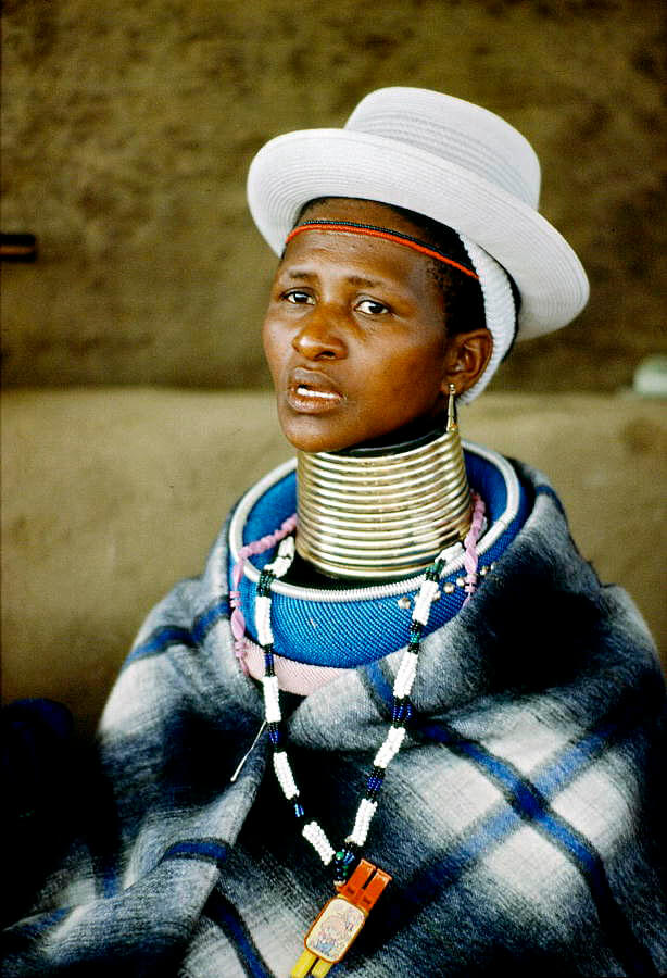 An Ndebele woman traditional neck ring attire and a Western-style hat. Flickr / United Nations Photo