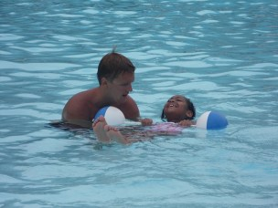 Children are gently guided around the water by their instructor