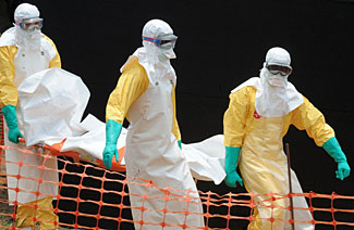 Healthcare workers in Africa carry out the dead body of an Ebola victim.