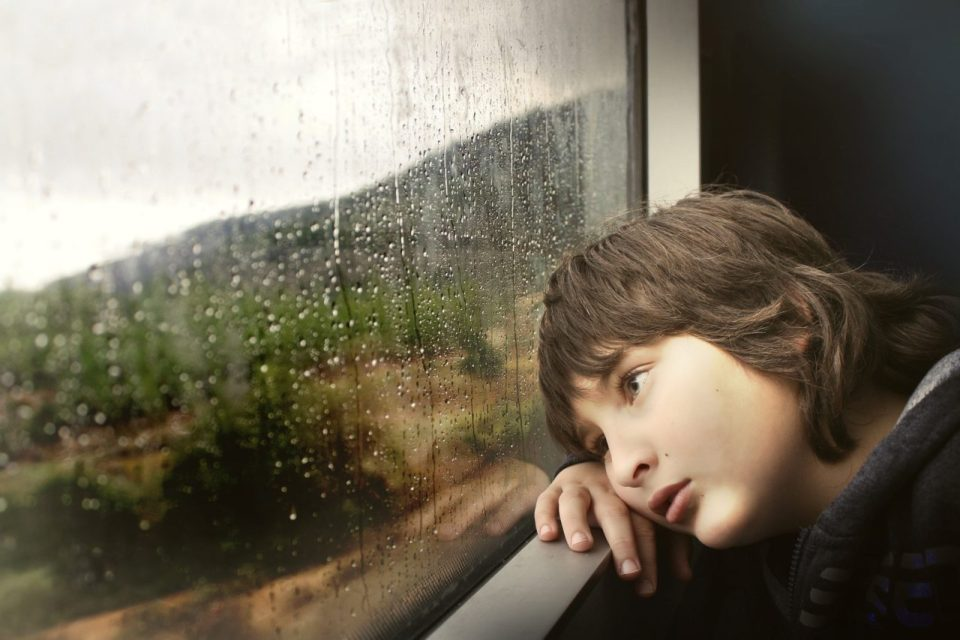 Boy leaning head against window of train or bus, looking outside. it's raining out.