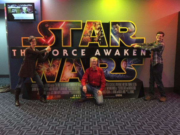 Joanna and Nick stand on either side of a large Star Wars: The Force Awakens poster, pantomiming wielding the lightsabers as if to strike their father Steve who sits crouched in front