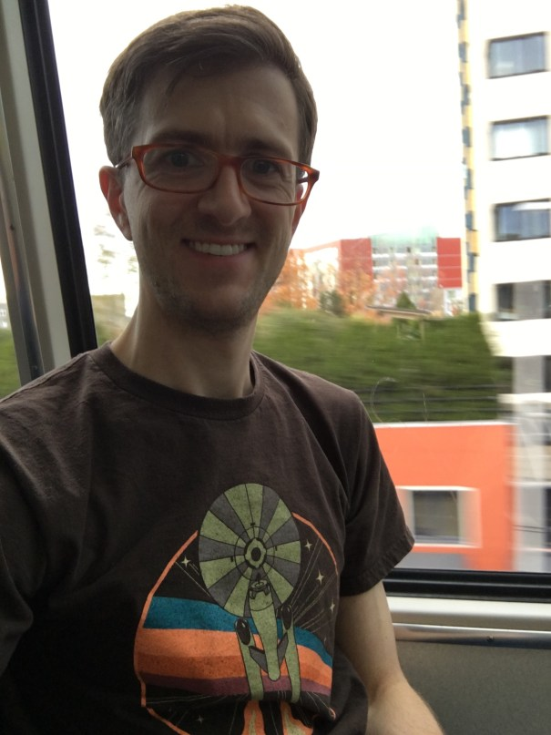 Selfie of Nick in a Star Trek tee riding the Monorail with Seattle zipping by in the background.