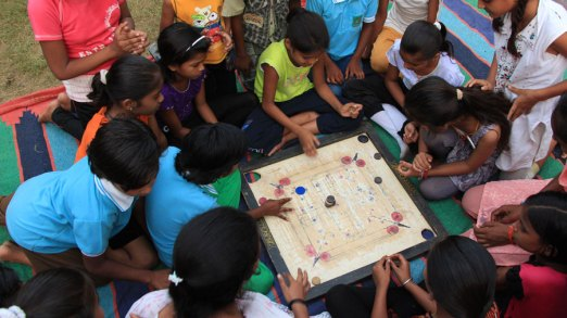 A crowd gathers to watch a game of Carom.