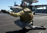 A catapult shooter signals the launch of an E-2C Hawkeye.
