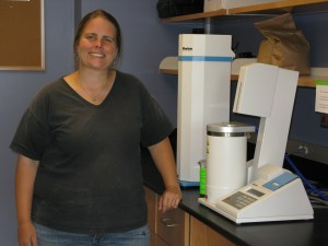 NWCS staffer Erica Cummings with Falling Number machine in UVM Extension Cereal Grains Testing Lab.