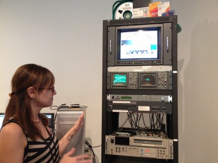 Kristin explains a basic transfer station setup, which includes playback decks, time-base corrector, a-d converter, waveform monitor, vectorscope, video monitor, capture card, and a computer with editing software.