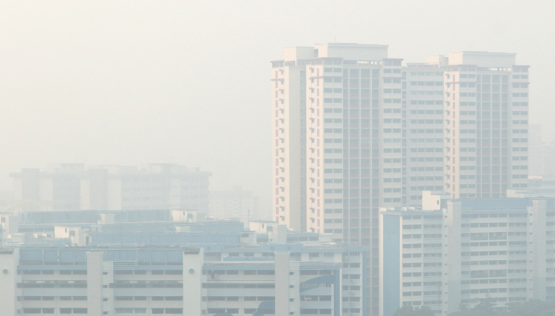 A general view of a housing estate covered by haze in Singapore. The haze was the result of illegal burning of forests and other land on Sumatra island in Indonesia' to make way for palm oil plantations and is causing Singaporeans to experience physical discomfort migraines, burning eyes, rashes, dry throats and runny noses and in cases of weaker individuals, asthma attacks and respiratory issues. Some offices and businesses have even suspended operations, to ensure their employees and customers are not exposed to the hazardous haze. Singapore''s air pollution soared to a record of 401 on the Pollutant Standards Index (PSI).