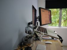 Laptop and monitor raised above the table top with the Ergotron arms