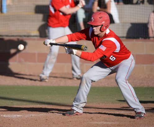 Regis batter Zach Woodruff put down a bunt to advance base runners in the sixth inning. The Regis Jesuit baseball team defeated Rock Canyon 10-1 Friday afternoon, April 11, 2014. (Karl Gehring, The Denver Post)