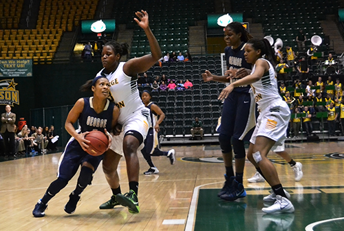 Then-junior guard Chakecia Miller squeezes pass a George Mason defender for a layup last season. File Photo by Aly Kruse | Hatchet Photographer