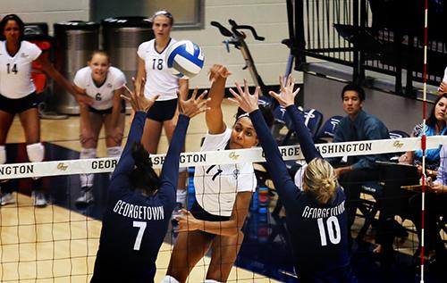 Then-freshman Aaliya Davidson spikes over two Georgetown blockers last season. GW plays Georgetown again on Sept. 15. File Photo by Kiana Robertson | Hatchet Photographer