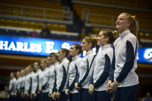 The Colonials welcome the many Brownies and Girl Scouts in attendance for the annual gymnastics meet held in their honor at the Smith Center.