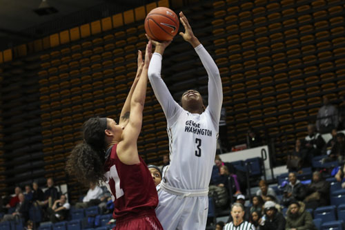 Junior forward Caira Washington puts up a shot against Massachusetts. Washington had 13 points in the 17-point victory. Jordan McDonald | Hatchet Staff Photographer