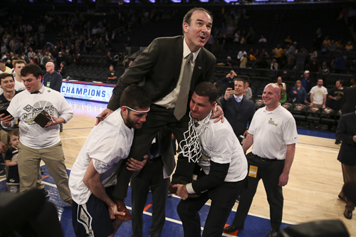 Senior Patricio Garino and and Assistant Director of Basketball Operations Chris Holm lift Head Coach Mike Lonergan as he cuts down one of the nets at Madison Square Garden. Dan Rich | Contributing Photo Editor