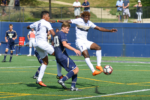 Juniors Christian Lawal (left) and Koby Osei-Wusu (right) look to make a play during GW's 1-0 win over Navy Sunday afternoon. Andrew Goodman | Senior Staff Photographer