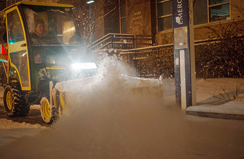 A worker plows the roads and sidewalks on campus Wednesday night. Hatchet File Photo