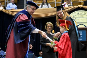 Michael Feuer, the dean of the Graduate School of Education and Human Development, presents a graduate's child with a scroll at the GSEHD celebration on Saturday. Zach Montellaro   Hatchet Staff Photographer