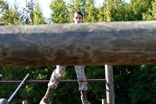 Freshman Genna Heaps prepares to jump over a log as she tackles the obstacle course for her first time.