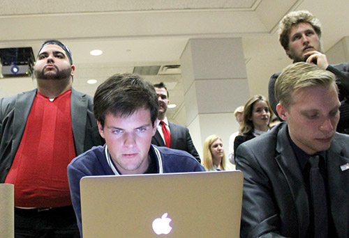 Freshman Reed Westscott tracks election results on his laptop as other members of the College Republicans watch election announcements on TV. Jordan McDonald | Hatchet Photographer