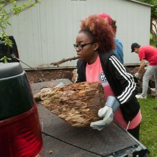 student loads firewood into truck