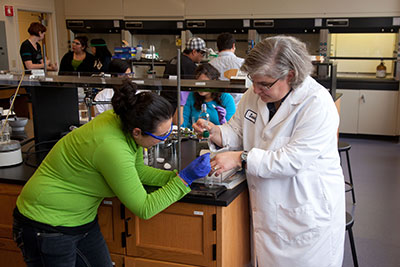 Female student with professor in science lab