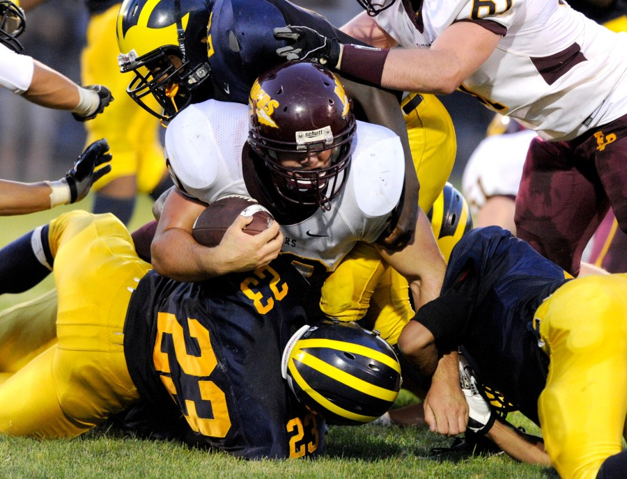ADAM GERIK/JOURNAL STAR  East Peoria's Jake Hornung (10) gets sandwiched by a trio of Woodruff defenders during Friday's game at Peoria Stadium.