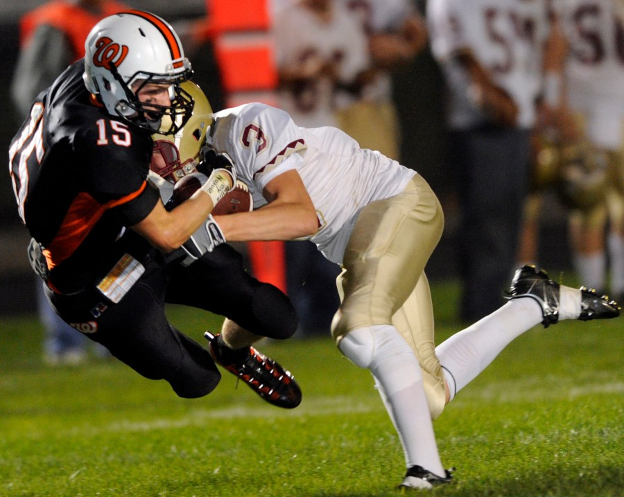 RON JOHNSON/JOURNAL STAR   Dunlap's Alex Fitzpatrick, right, takes Washington's Drew Schlink off his feet on this hit during Friday night's game.