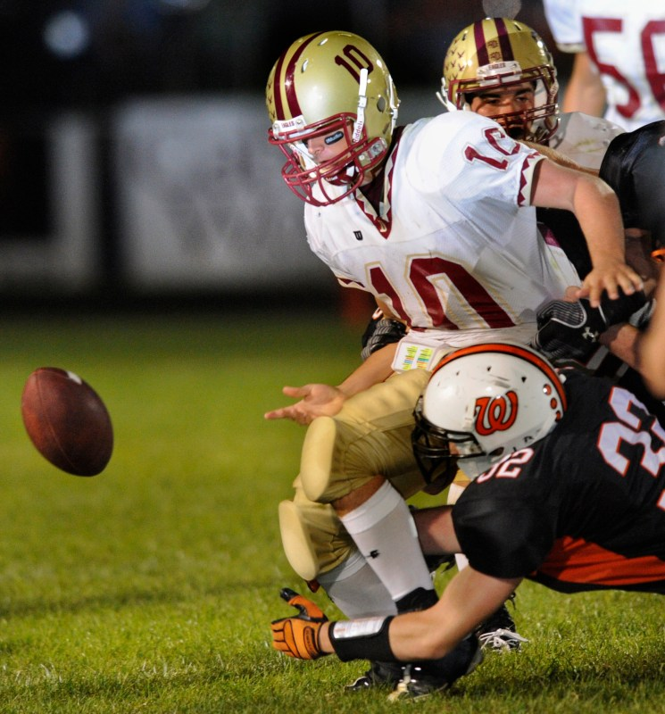 RON JOHNSON/JOURNAL STAR  Washington's Eric Jaszarowski, bottom, forces Dunlap quarterback Logan Schrader to fumble the ball during Friday night's game.