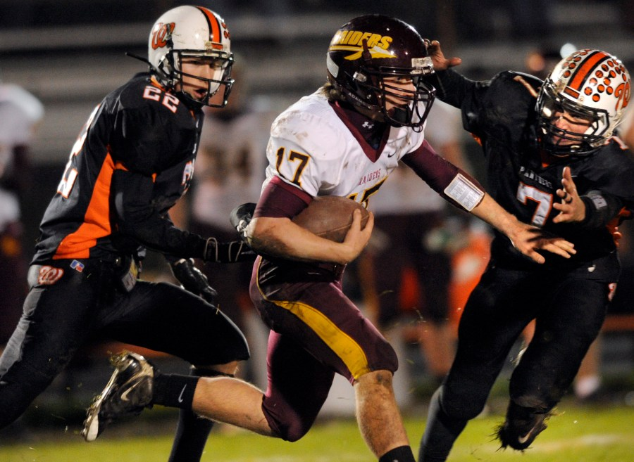RON JOHNSON/JOURNAL STAR  East Peoria quarterback Andrew Wallace(17) tries to elude Washington's Ryan Grebner (22) and Isaac Fisher (7) on a run in the fourth quarter of Friday's game.