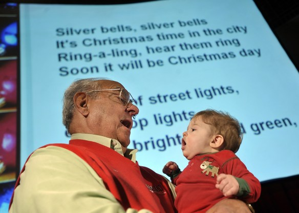 RON JOHNSON/JOURNAL STAR  Jim Maloof and his 7-month old grandson, Ethan Maloof, combine voices in Thursday evening's Journal Star Family Christmas Sing inside the Great Hall of the Peoria Civic Center in 2008.