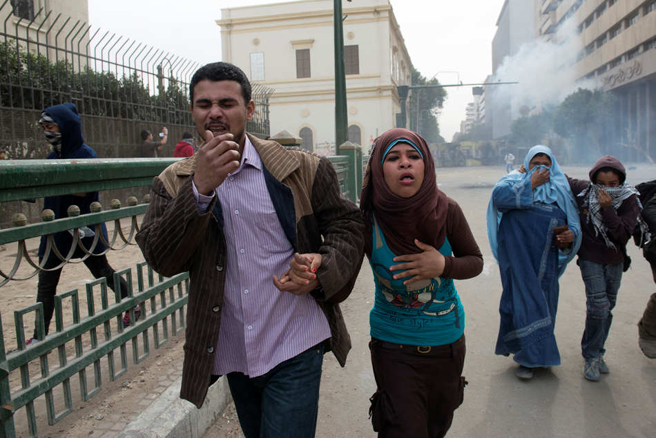 Egyptians flee teargas during a clash with police in Tahrir Square in Cairo on Thursday Jan. 24, 2013, the eve of the the second anniversary of the uprising that overthrew Hosni Mubarak.(AP Photo/Tribune Review, Jusstin Merriman)  PITTSBURGH OUT