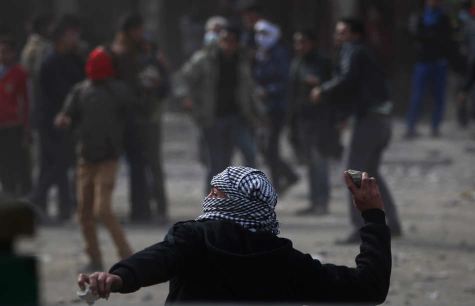 Egyptian protesters throw stones at riot police, not seen, during clashes near Tahrir Square, Cairo, Egypt, Friday, Jan. 25, 2013. Egyptian opposition protesters are gathering in Cairo's Tahrir Square to mark the second anniversary of the uprising that toppled Hosni Mubarak's autocratic regime. (AP Photo/Khalil Hamra)