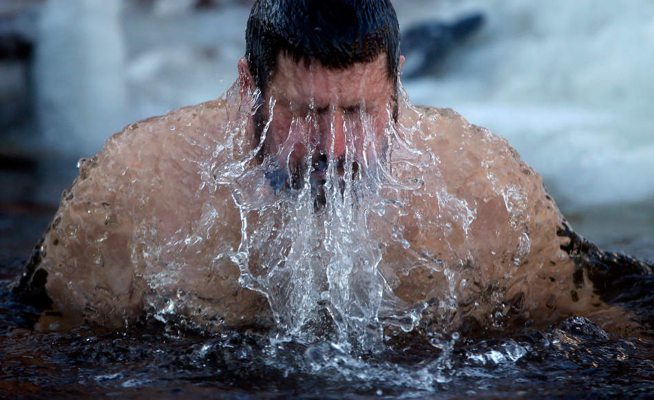 A man plunges in the ice cold water to mark Epiphany, in St.Petersburg, Russia, Saturday, Jan. 19, 2013.  The temperature in St. Petersburg is -22C (  -7.6 ° F). Thousands of Russian Orthodox Church followers plunged into icy rivers and ponds across the country to mark Epiphany, cleansing themselves with water deemed holy for the day. Water that is blessed by a cleric on Epiphany is considered holy and pure until next year's celebration, and is believed to have special powers of protection and healing. (AP Photo/Dmitry Lovetsky)